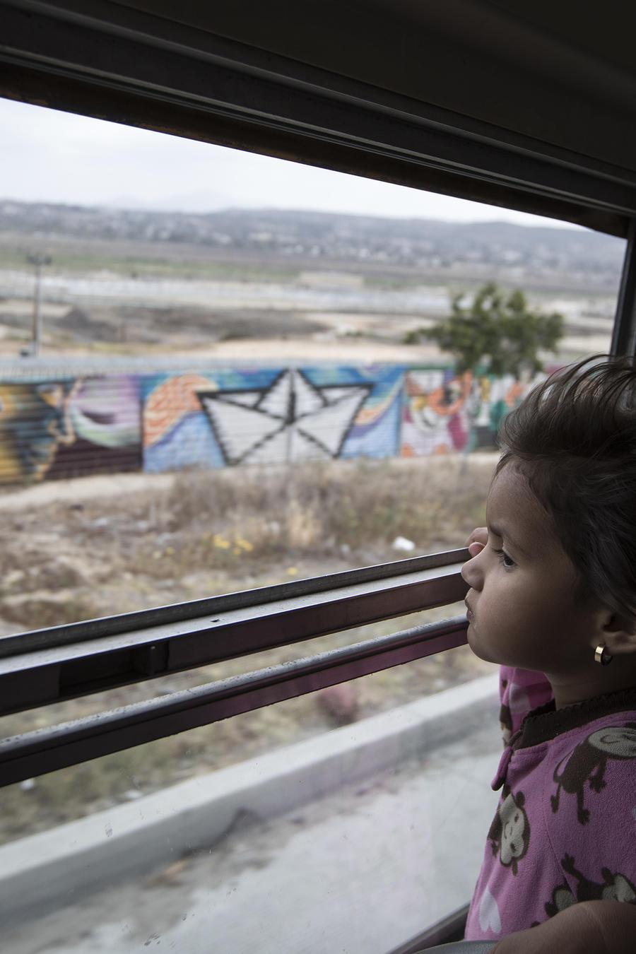 Una niña migrante centroamericana mira el muro fronterizo en Tijuana, México, el 29 de abril de 2018.