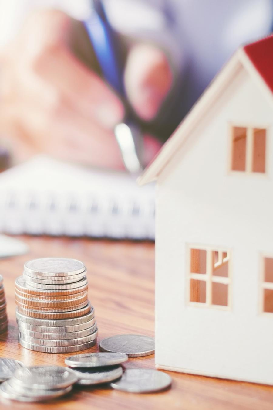 Monedas, casa y persona escribiendo