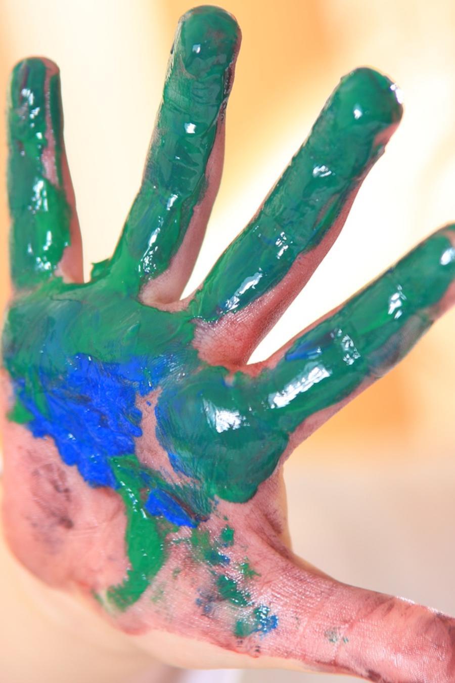 Niña con mano sucia con pintura