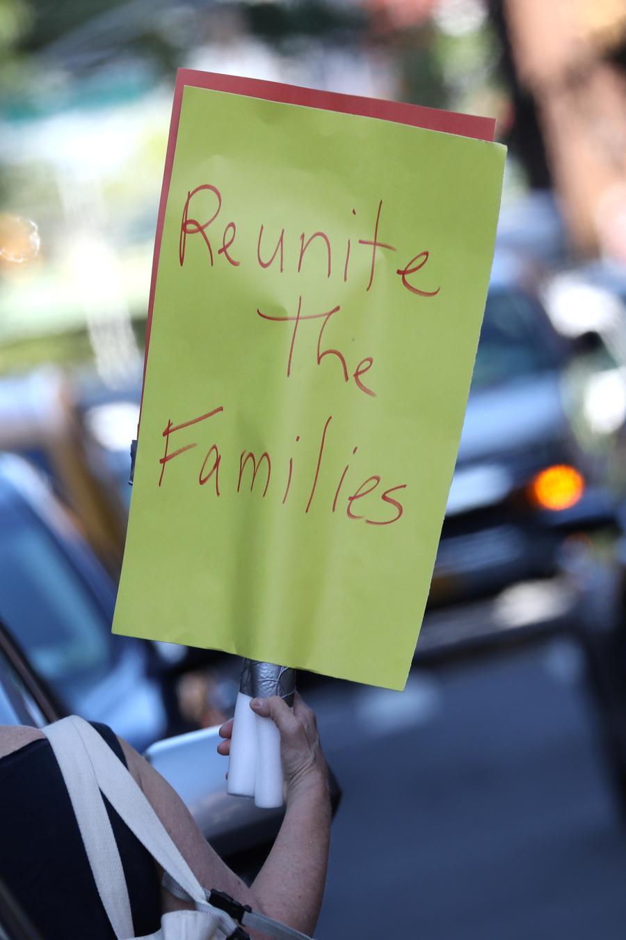Una mujer lleva consigo un letrero en las afueras del Centro Cayuga que alberga niños separados de sus familias en Nueva York