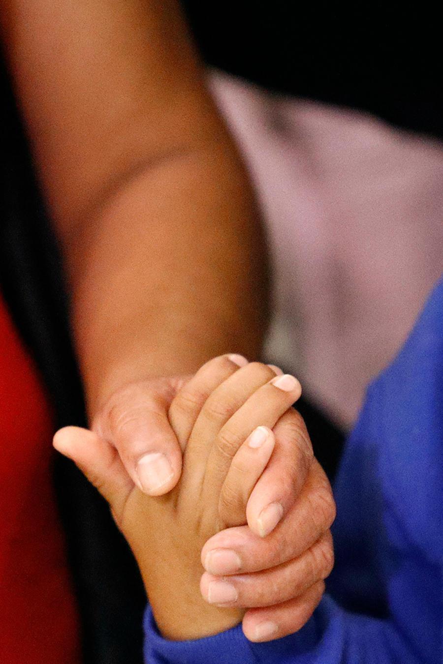 Una madre indocumentada le da la mano a su niño tras pasar meses separados