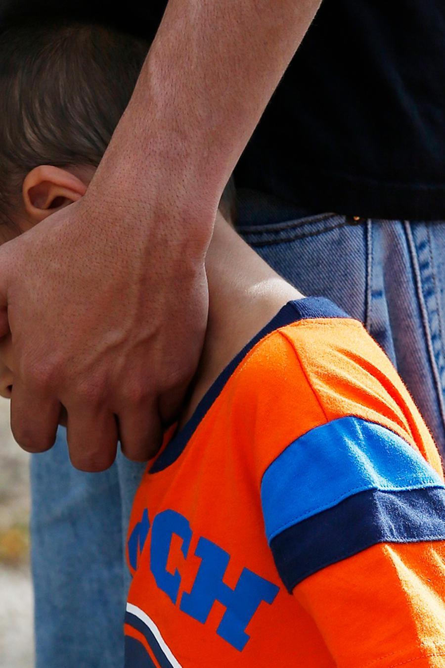Un niño de honduras que había sido separado de su padre camina junto a él tras ser reunidos en Phoenix el 10 de julio de 2018