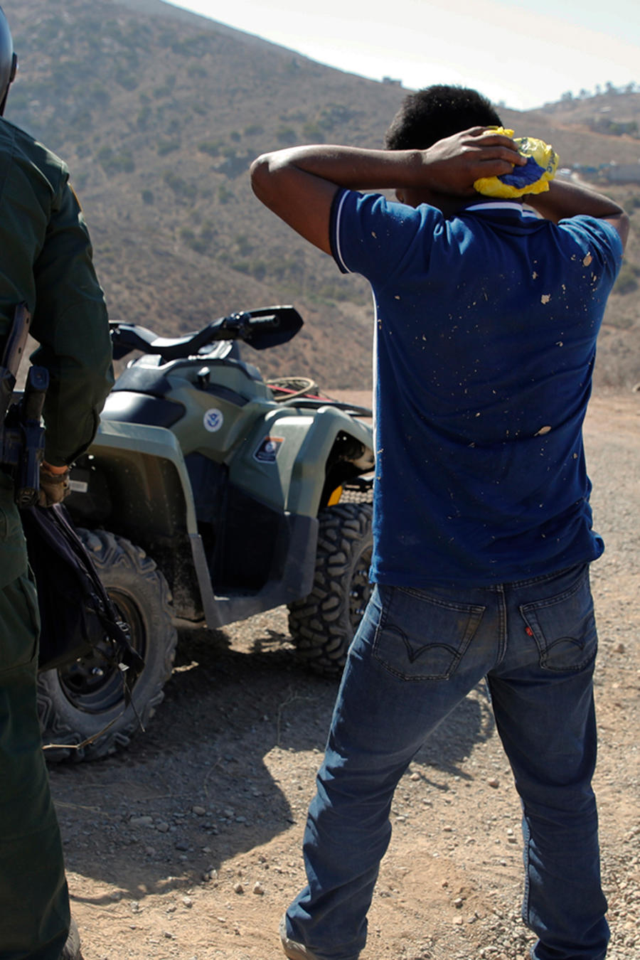Un patrullero de la frontera detiene a un inmigrante que cruzó ilegalmente al frontera con su hijo el 28 de junio de 2018
