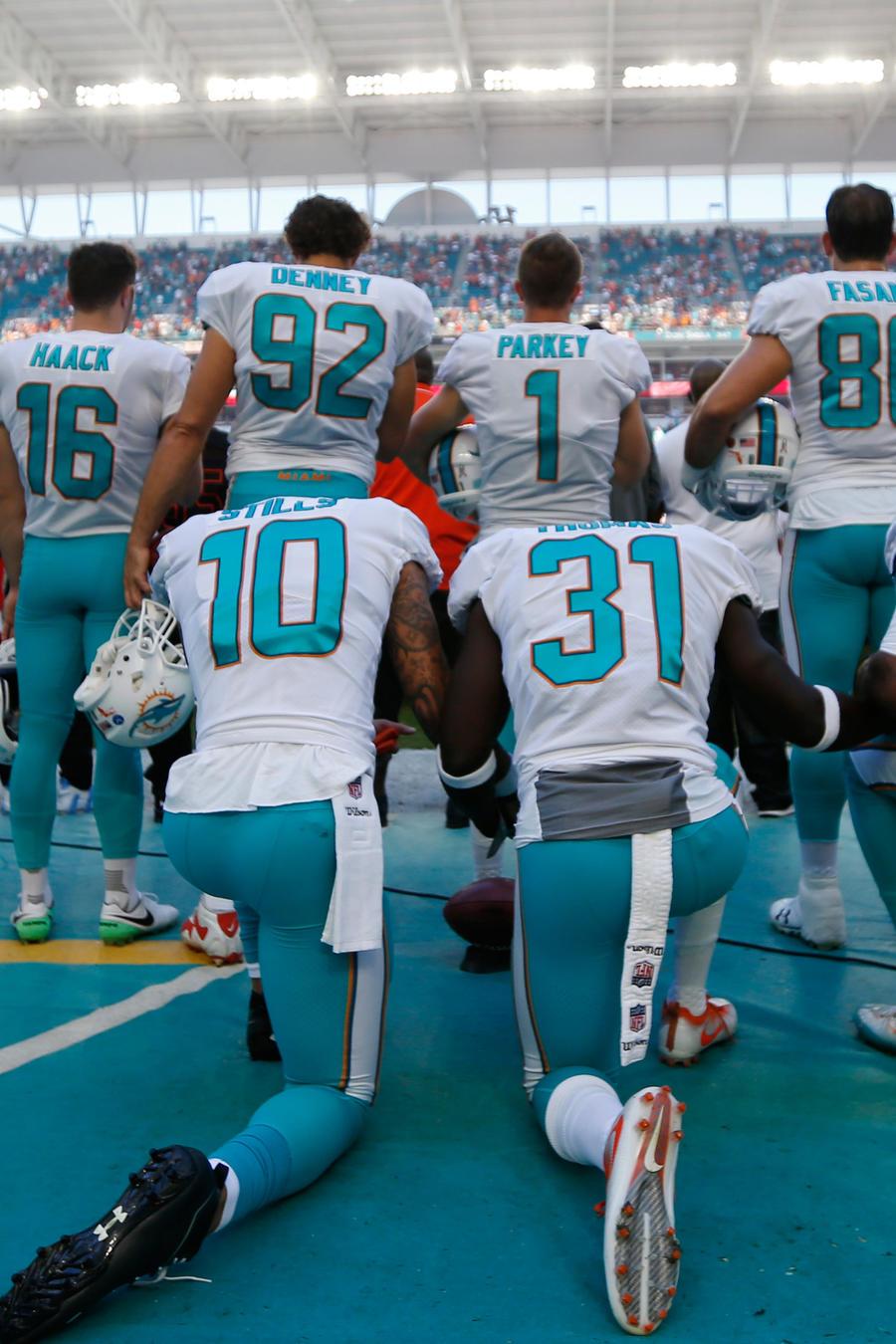 Jugadores de la NFL arrodillados mientras suena el himno nacional de EEUU