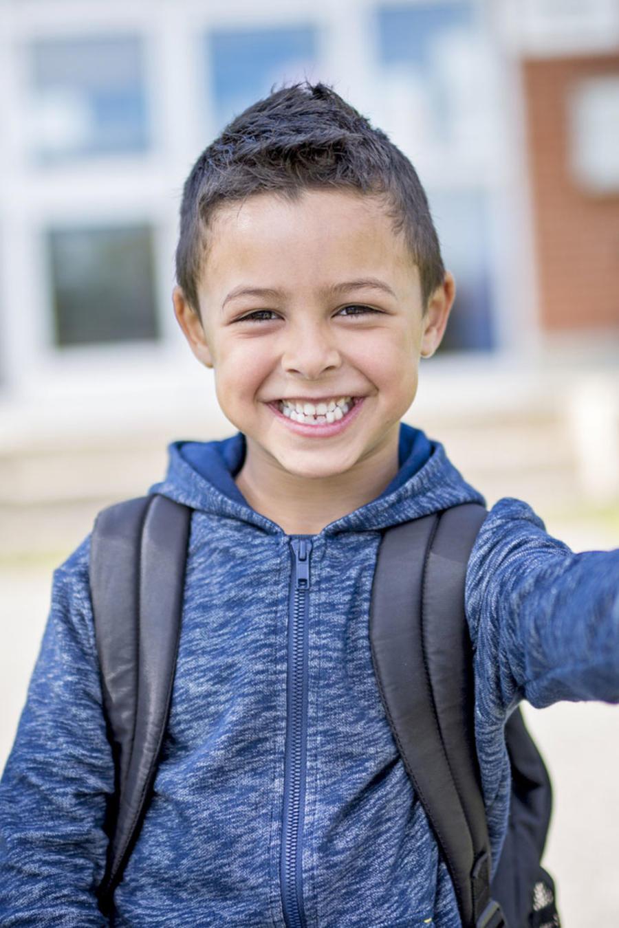 Niño sonriendo con el pulgar arriba