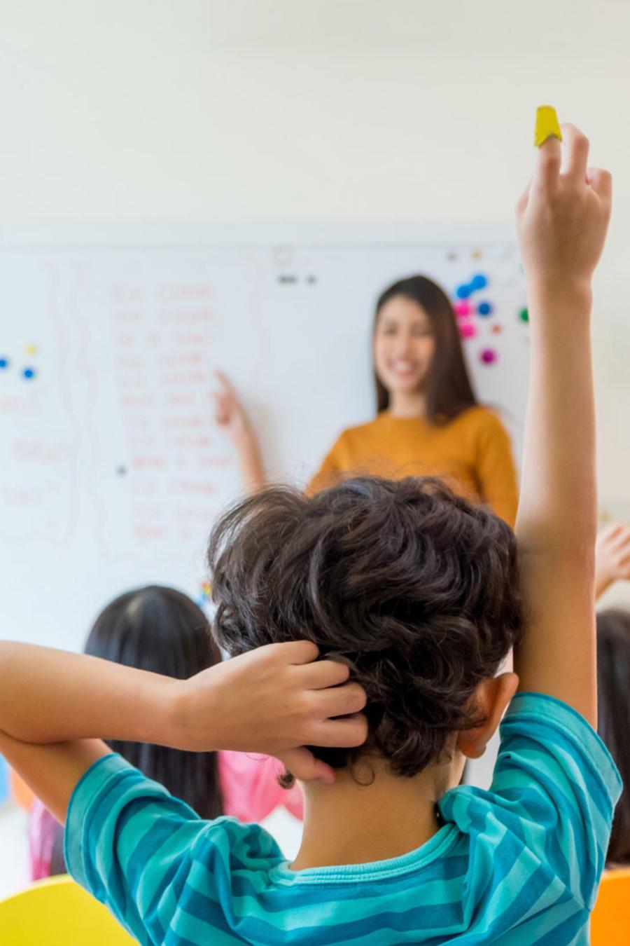 Niños en el aula, levantando la mano