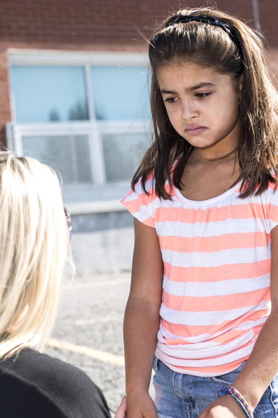 Mujer hablando con una niña triste