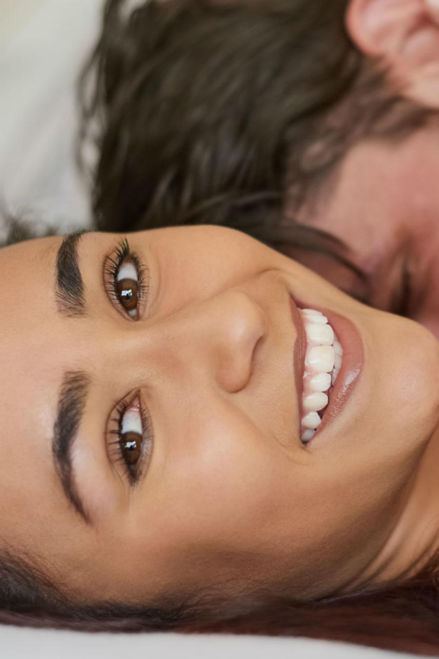 Mujer sonriendo, con su pareja en la cama