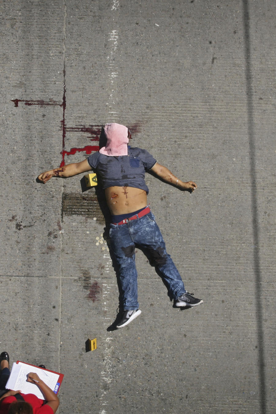 Investigadores federales analizan un cadáver tiroteado a plena luz del día en Acapulco en agosto de 2017.