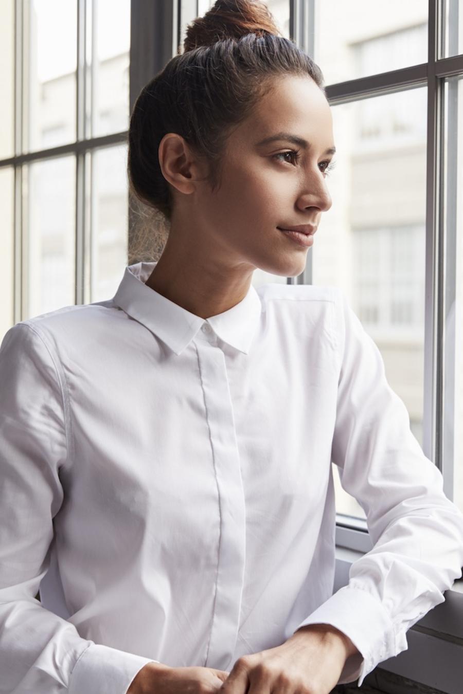 Chica con camisa mirando por la ventana