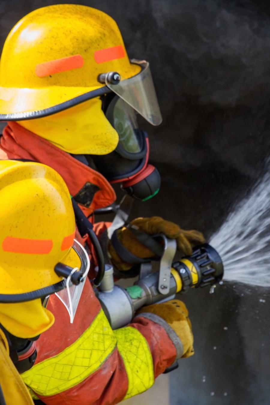 Dos bomberos usando una manguera