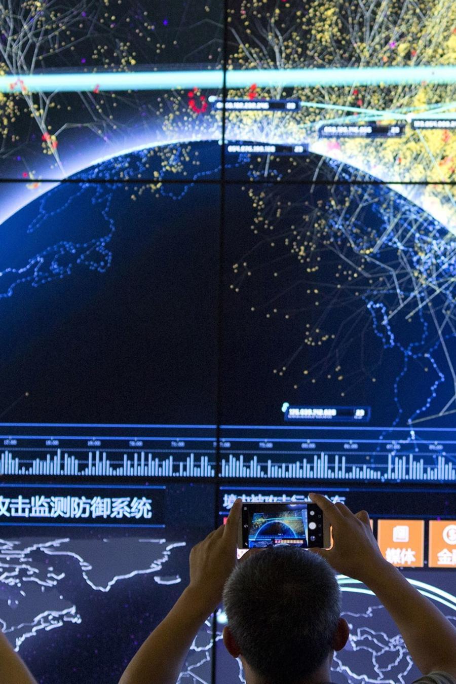 Un asistente toma una foto de una visualización de los ataques globales de Internet durante la 4ta Conferencia de Seguridad de Internet de China en Beijing el 16 de agosto de 2016.
