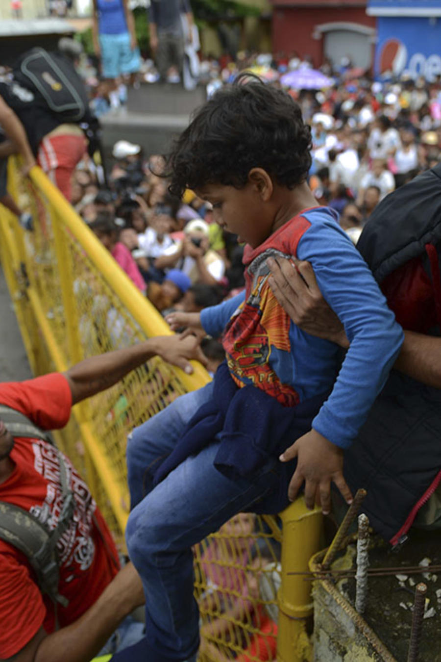 Dos adultos ayudan a un niño a cruzar una cerca en la frontera de México y Guatemala.