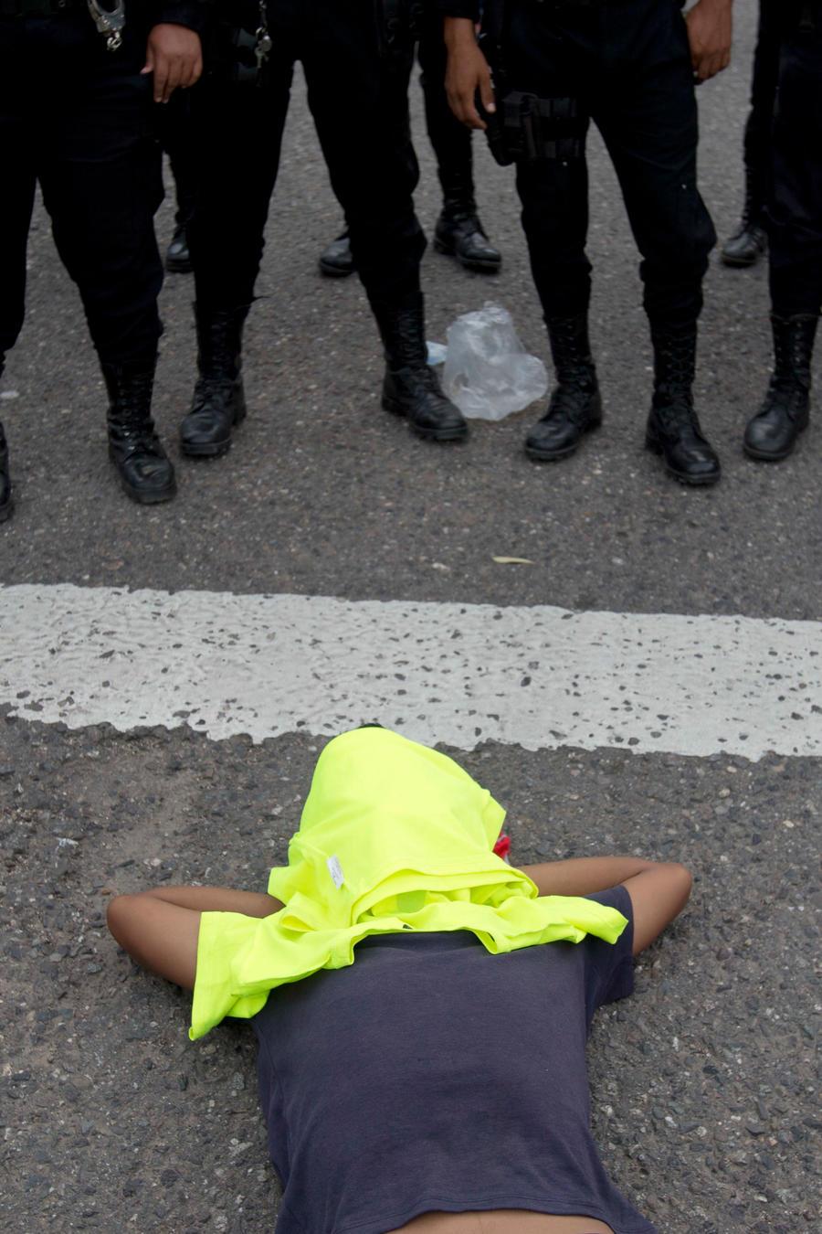 Un hondureño tumbado en el suelo en frente de la policía de Guatemala que cortó temporalmente el paso a los intergrantes de la caravana de migrantes