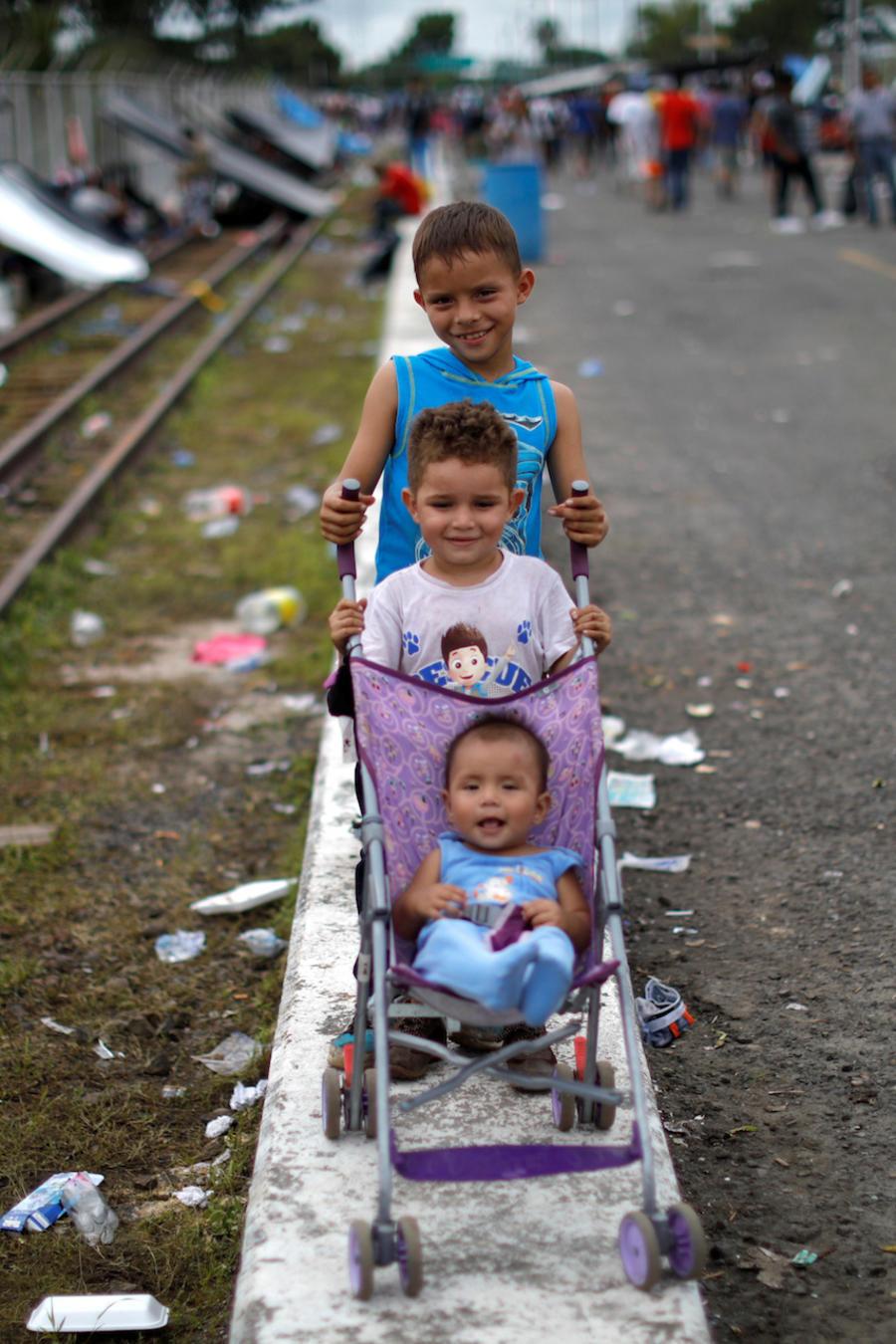 Tres niños hondureños que forman parte de la caravana, el viernes en Tecun Uman, Guatemala.