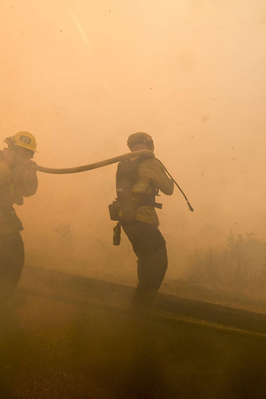Dos bomberos combaten las llamas del voraz incendio forestal en Simi Valley, California.