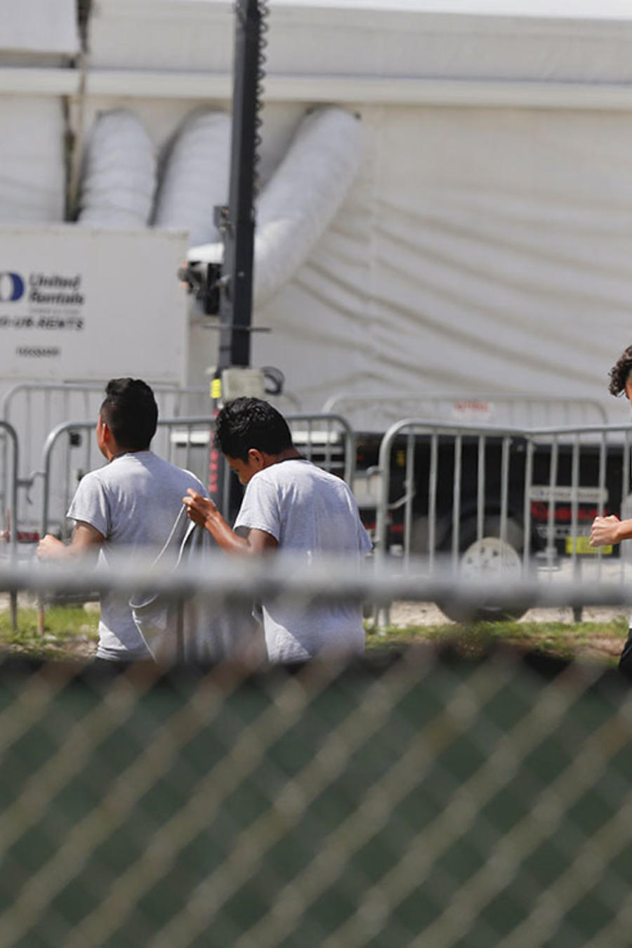 Menores migrantes caminan en las afueras del Migrant Homestead Temporary Shelter for Unaccompanied Children, en Homestead, Florida.