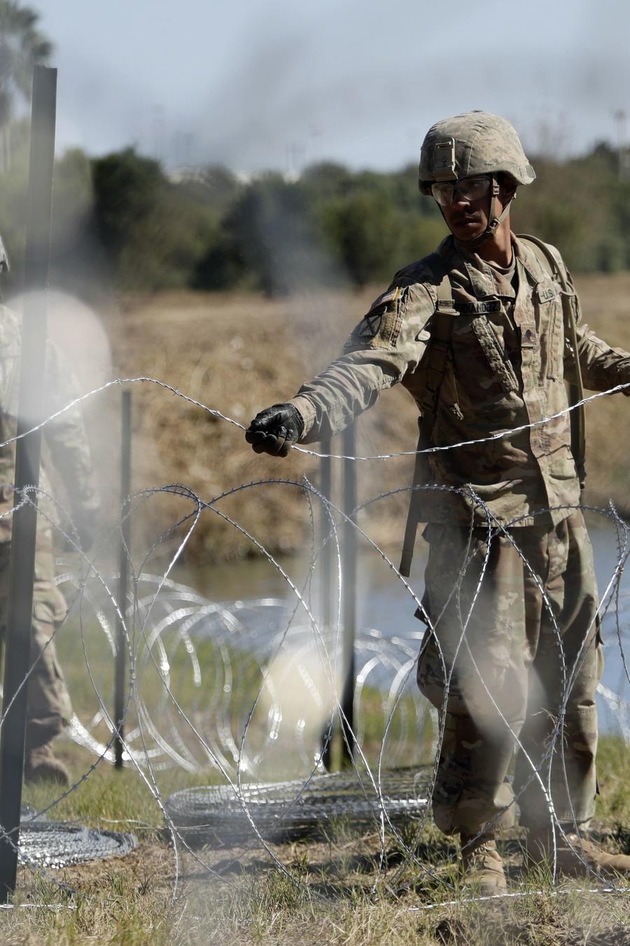 Miembros de las fuerzas armadas estadounidenses instalan varios niveles de cable de concertina