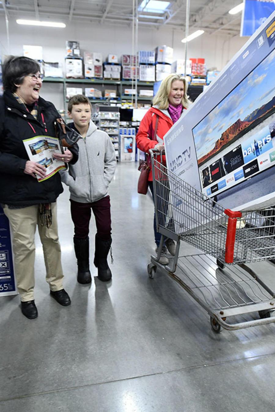 Una familia se dirige a la caja registradora tras haber comprado un televisor en oferta por el Bclak Friday.