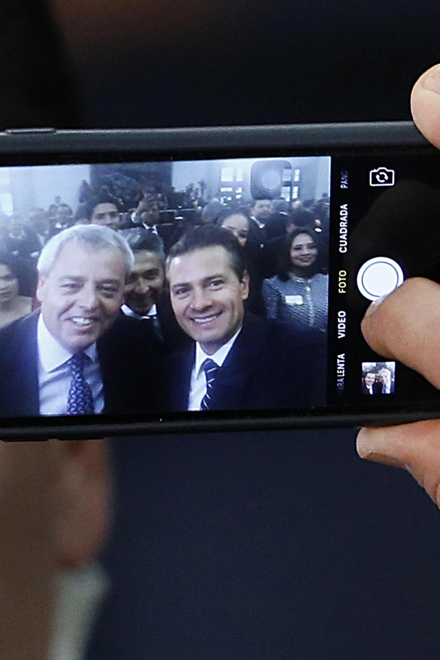 En esta foto de archivo aparece el presidente de México, Enrique Peña Nieto a la derecha, acompañado del director de Pemex, René Curiel en un teléfono.