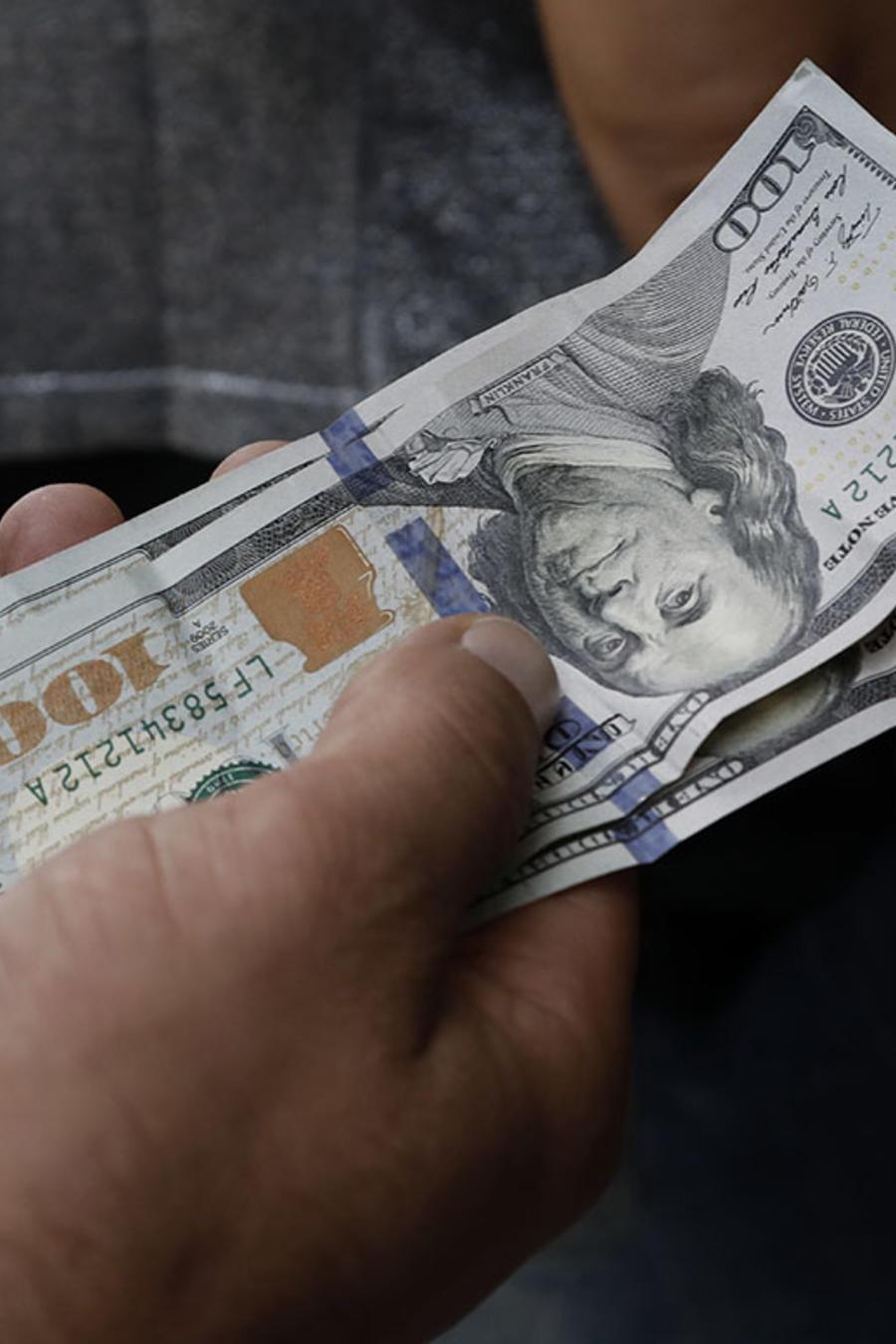 Un hombre sostiene en sus manos varios billetes de 100 dólares americanos.