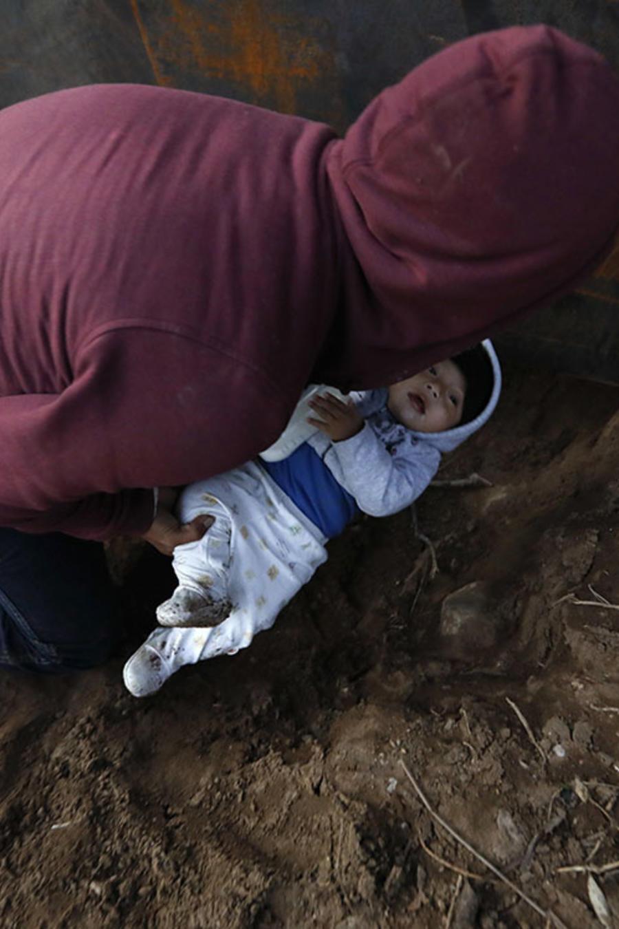 El migrante hondureño Joel Méndez, de 22 años, trata de pasar a su hijo de ocho meses por un agujero entre la frontera de Estados Unidos y México.