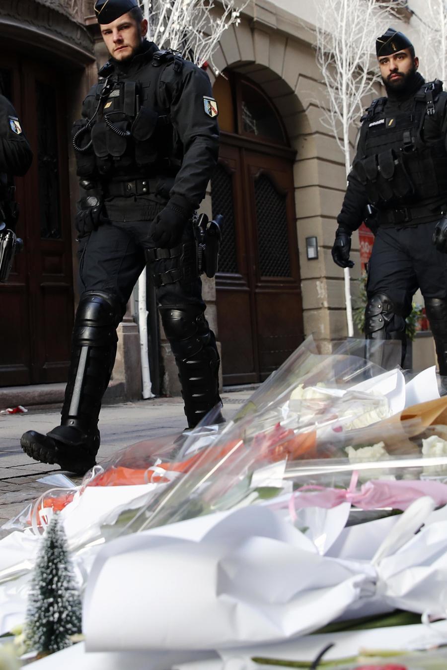 Policías caminan frente a un altar improvisado por las víctimas de un ataque terrorista en Estrasburgo en diciembre de 2018