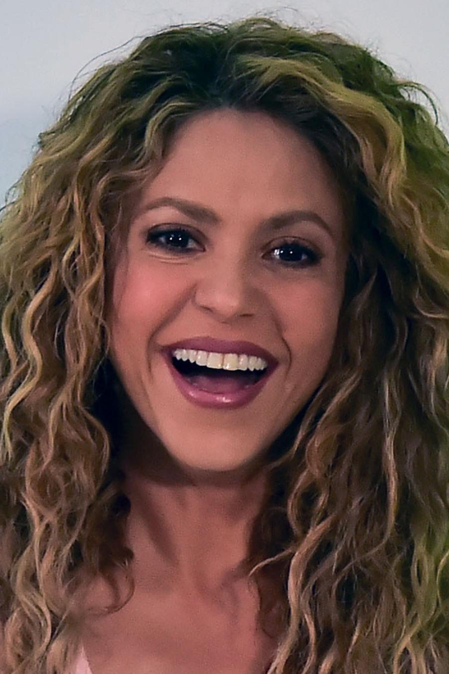 Shakira smiles and waves