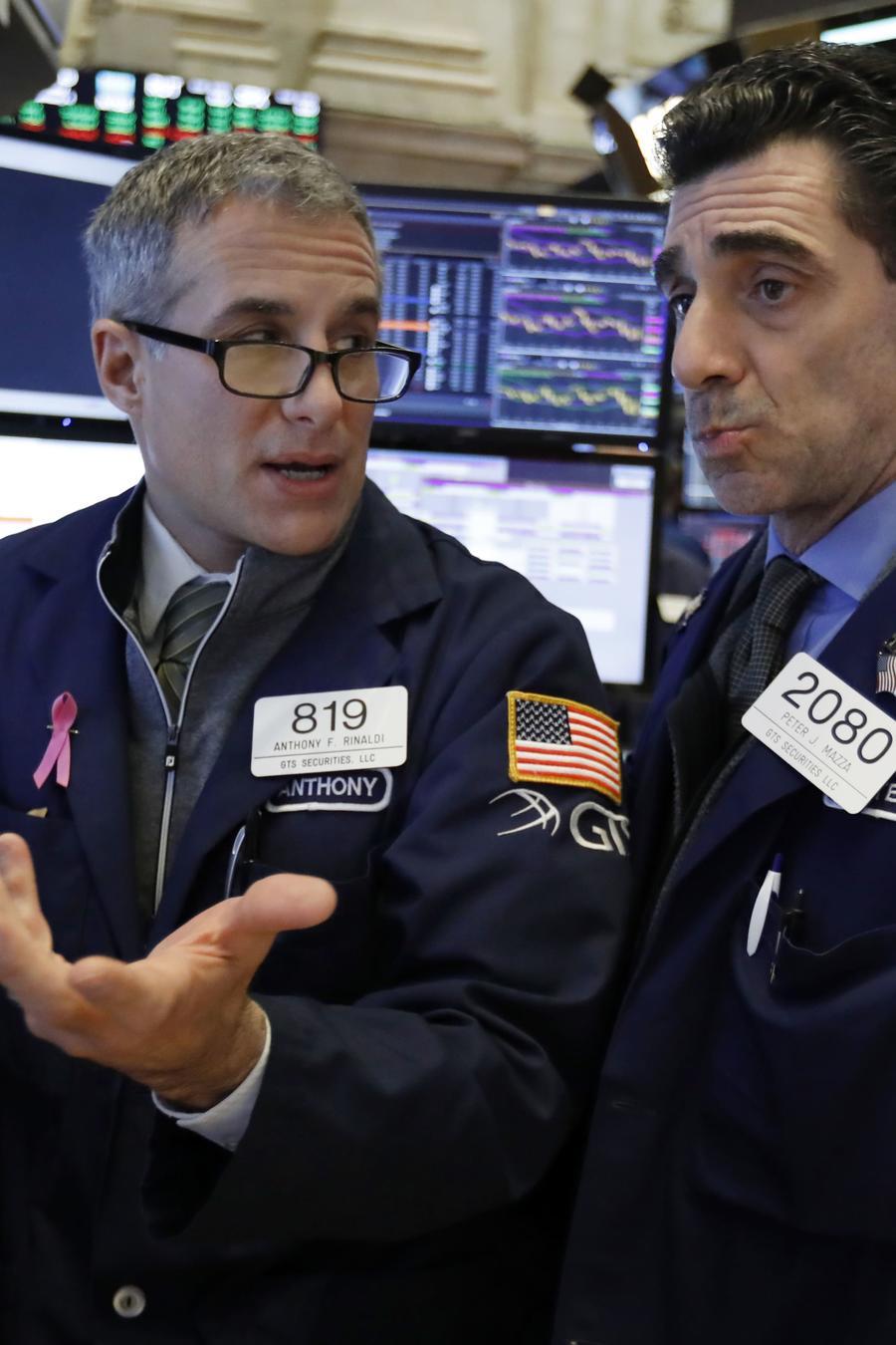 Los especialistas Anthony Rinaldi, a la izquierda, y Peter Mazza consultan mientras trabajan en el piso de la Bolsa de Nueva York