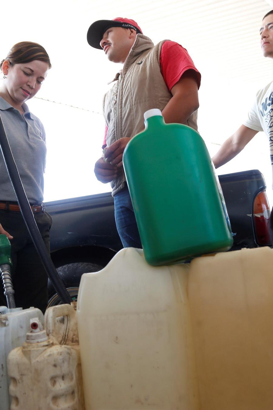 Usuarios se abastecen de combustible en una gasolinera de la ciudad de Guadalajara, en México).