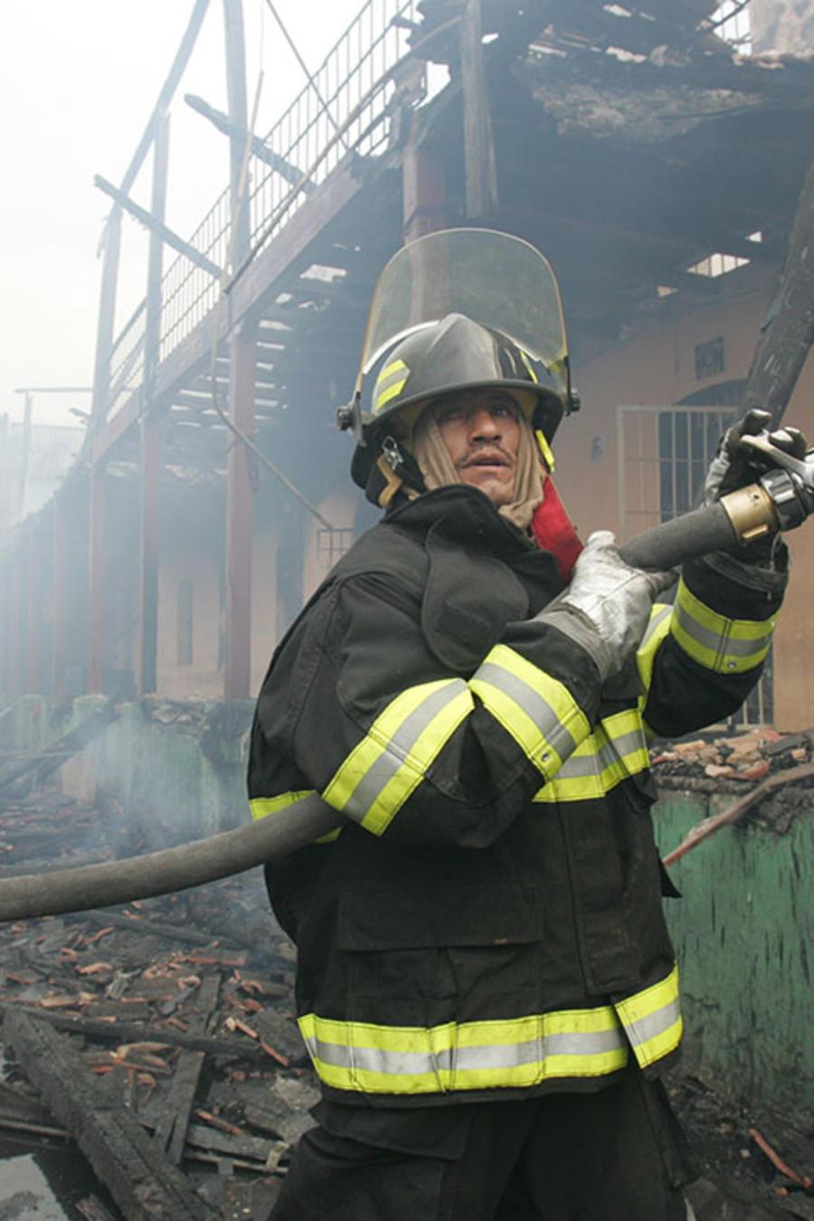 En esta imagen de archivo, dos bomberos ecuatorianos trabajan para socavar un incendio.
