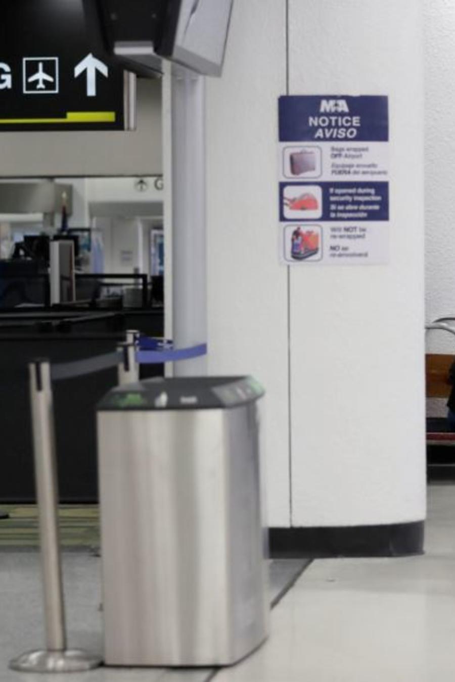 Viajeros esperan cerca de una terminal cerrada en el Aeropuerto Internacional de Miami este sábado 12 de enero de 2019.