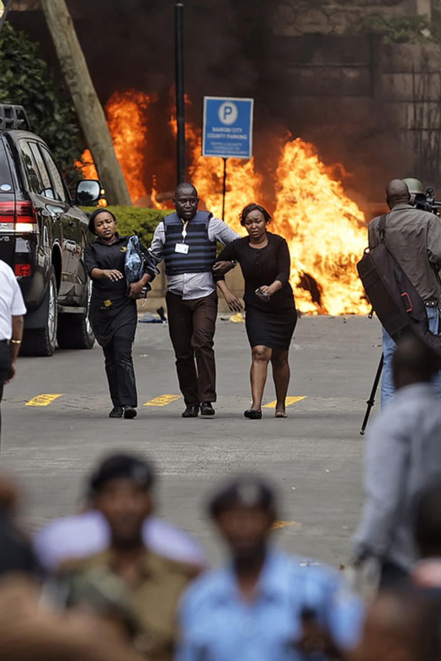 Fuerzas de seguridad ayudan a los civiles a huir de la escena del atentado terrorista en un complejo hotelero en Nairobi, Kenia.
