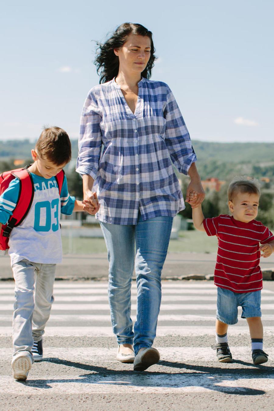 Mujer lleva a sus hijos a la escuela