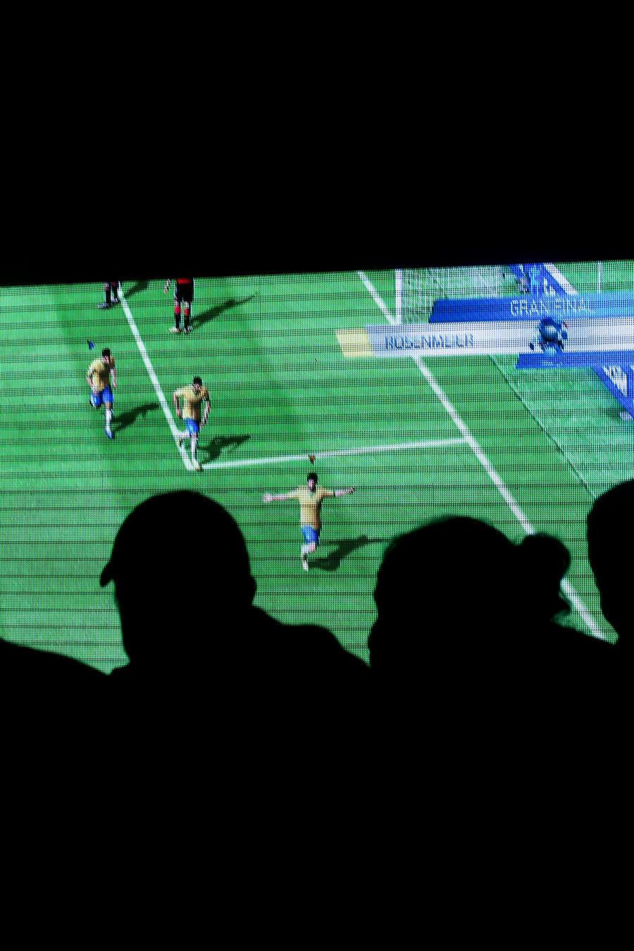 Fotografía de unas personas mirando un partido de fútbol en el Mundial de Brasil 2014.