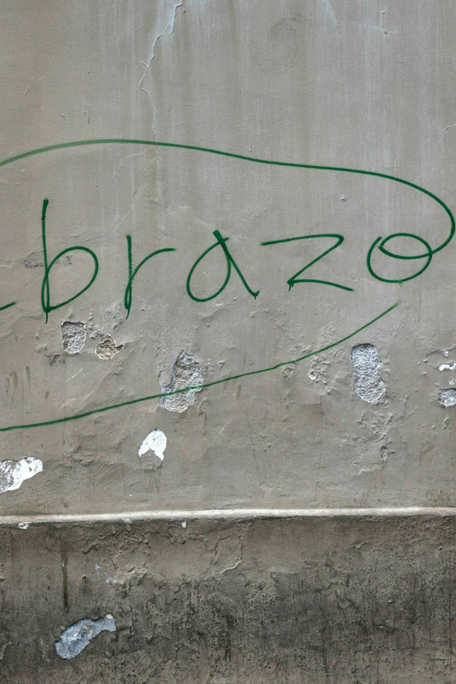 Una mujer en una calles de Caracas ante una pared donde aparece escrita la palabra abrazo