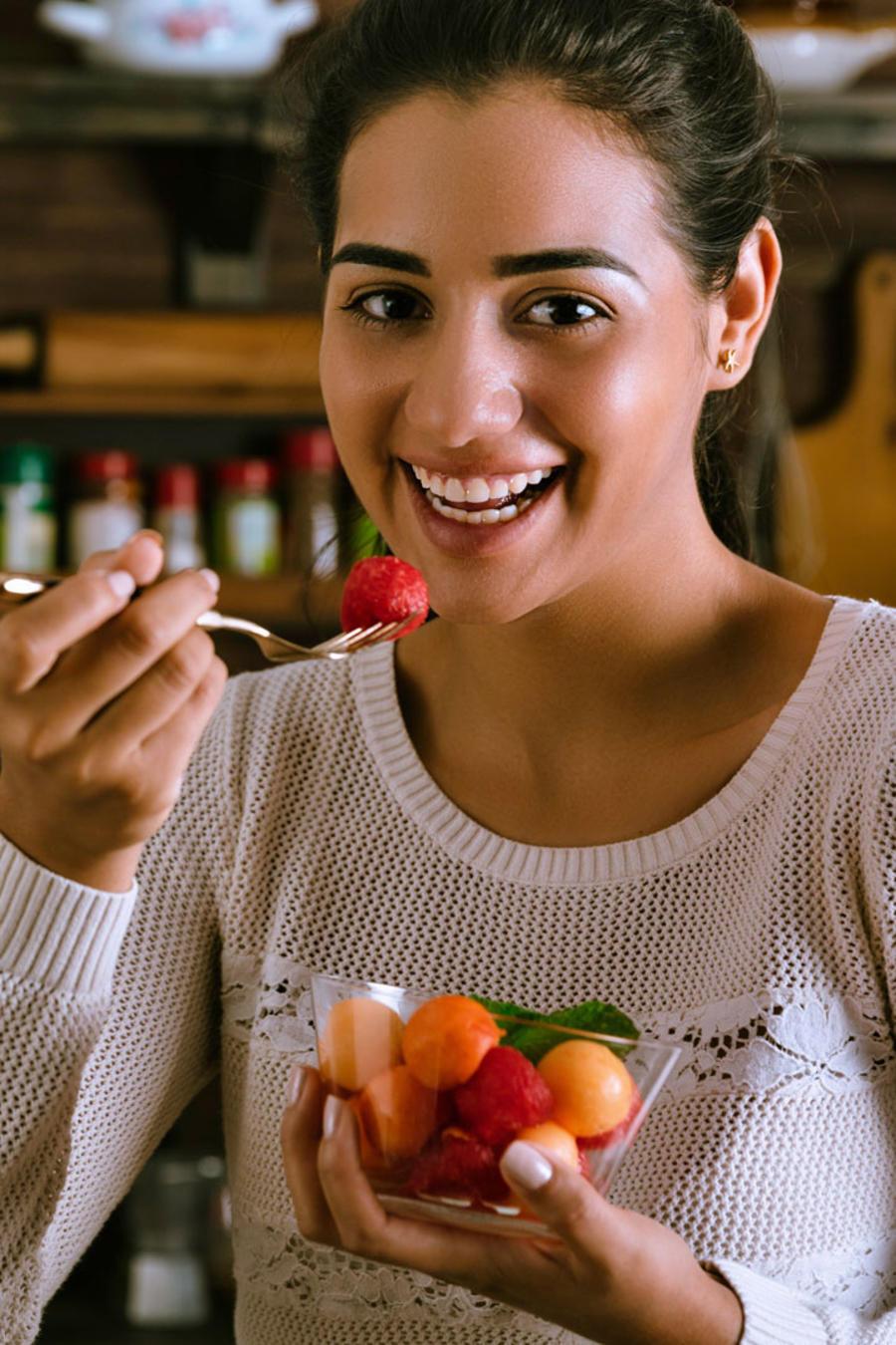 Chica comiendo una ensalada de frutas