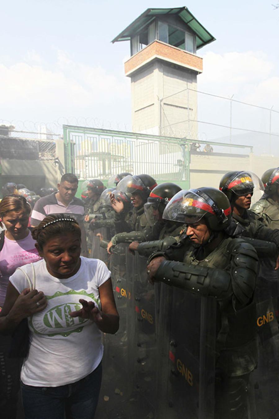 En esta imagen de archivo, familiares de presos caminan al lado de una barrera de soldados de la Guardia Nacional de Venezuela durante un incidente en una cárcel en Caracas.