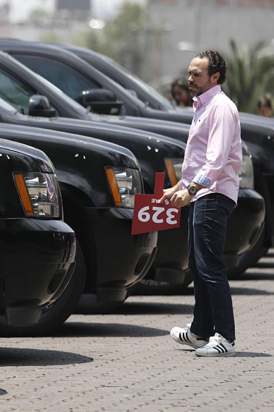 Un hombre sostiene su paleta de subasta mientras mira autos en el Centro Cultural Los Pinos, que fuera residencia presidencial, en Ciudad de México.