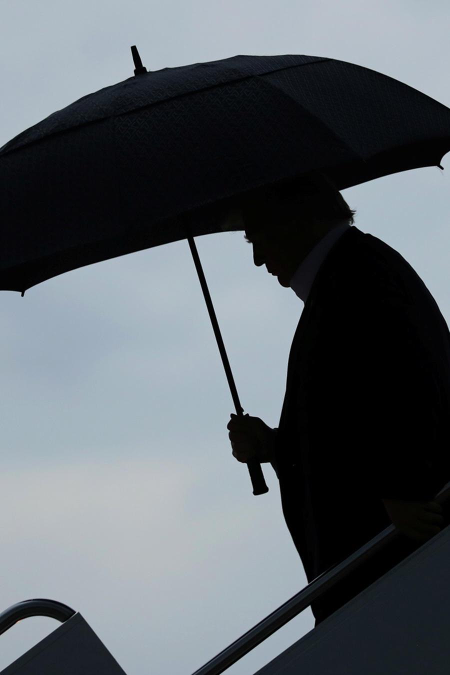 El presidente de EEUU, Donald Trump, desciende del avión presidencial con un paraguas