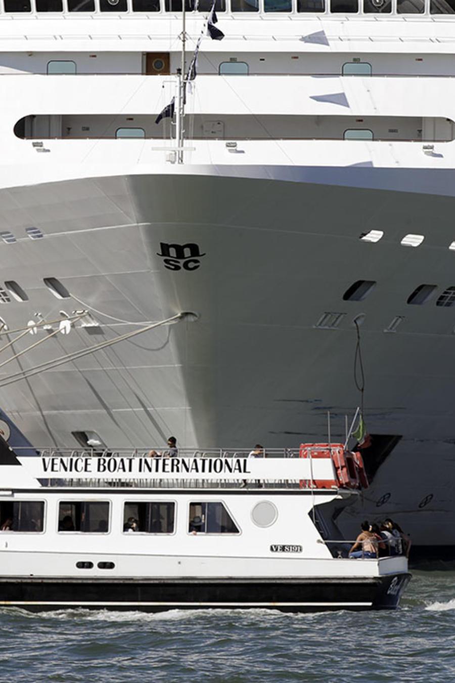 Un peuqeño bote pasa por delante del crucero MSC Opera en Venecia, Italia.