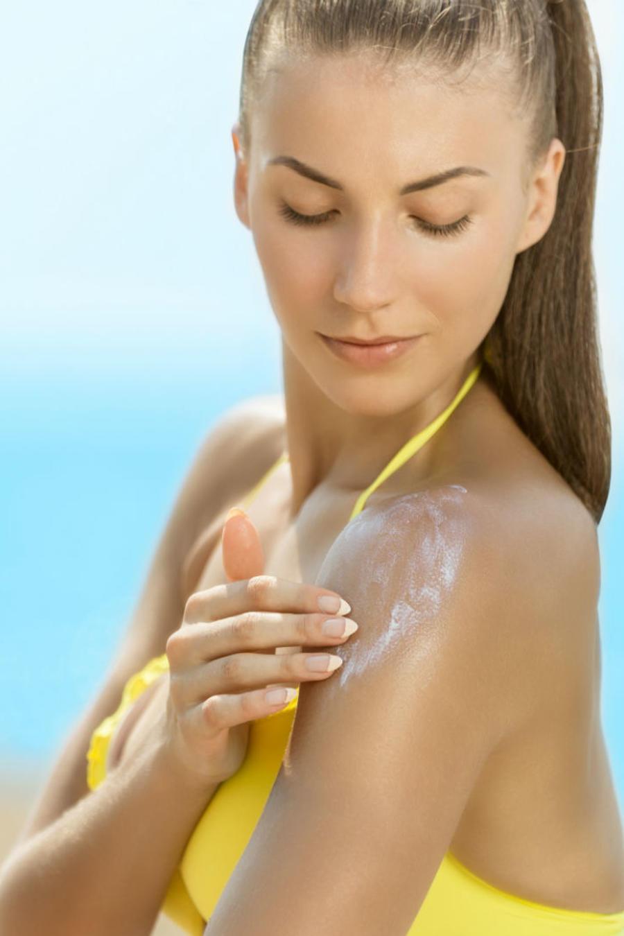 Mujer en la playa aplicándose bloqueador