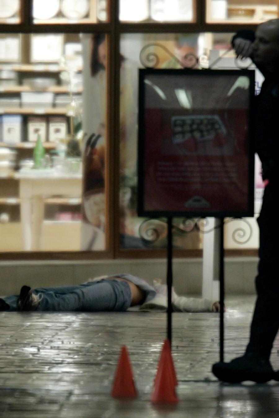 En esta fotografía de archivo de 2007 un policía vigila el sitio donde quedó tendido el cuerpo de una mujer tras el tiroteo en el centro comercial de Trolley Square