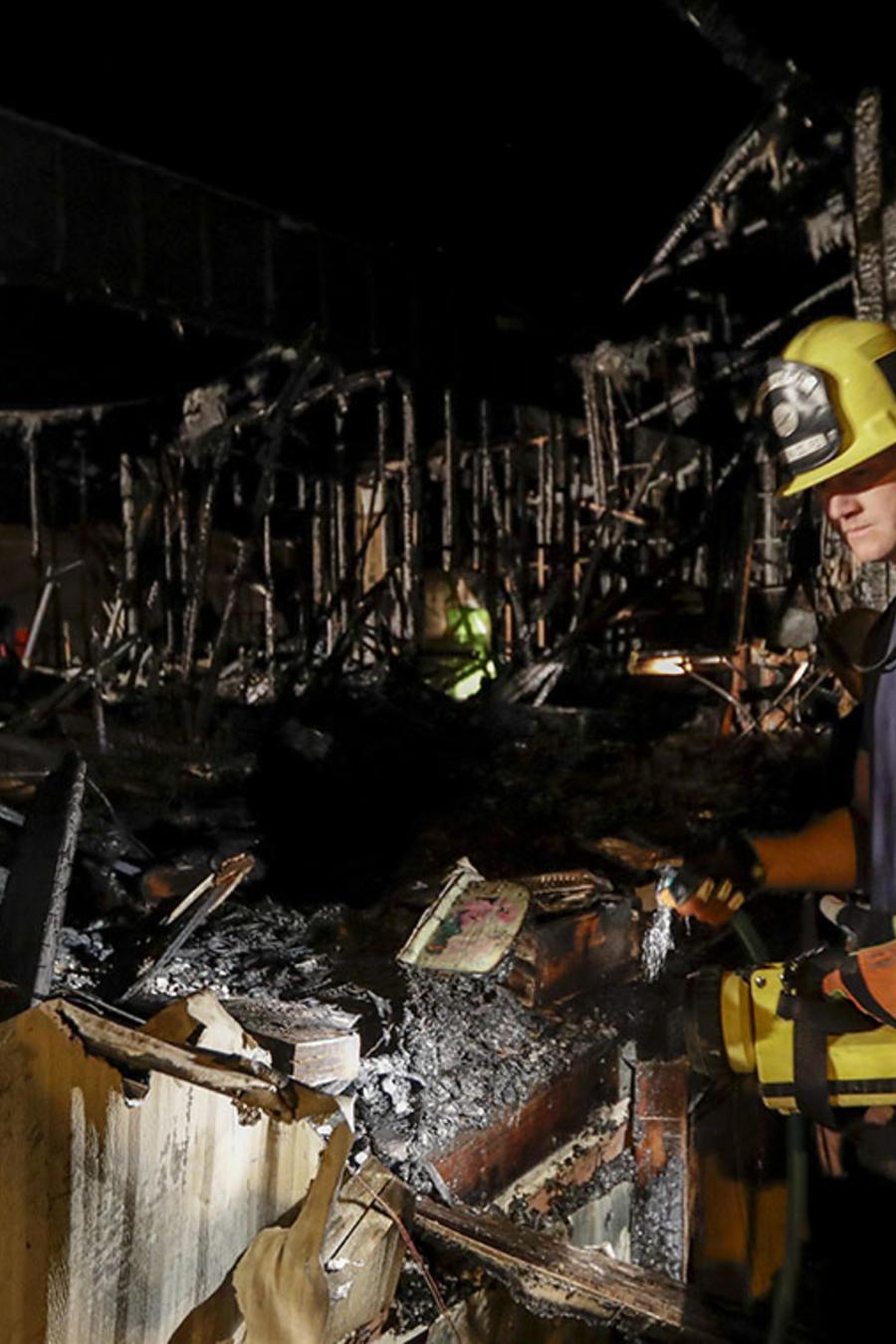 Un bombero revisa los escombros de una casa que se desplomó debido a un incendio.