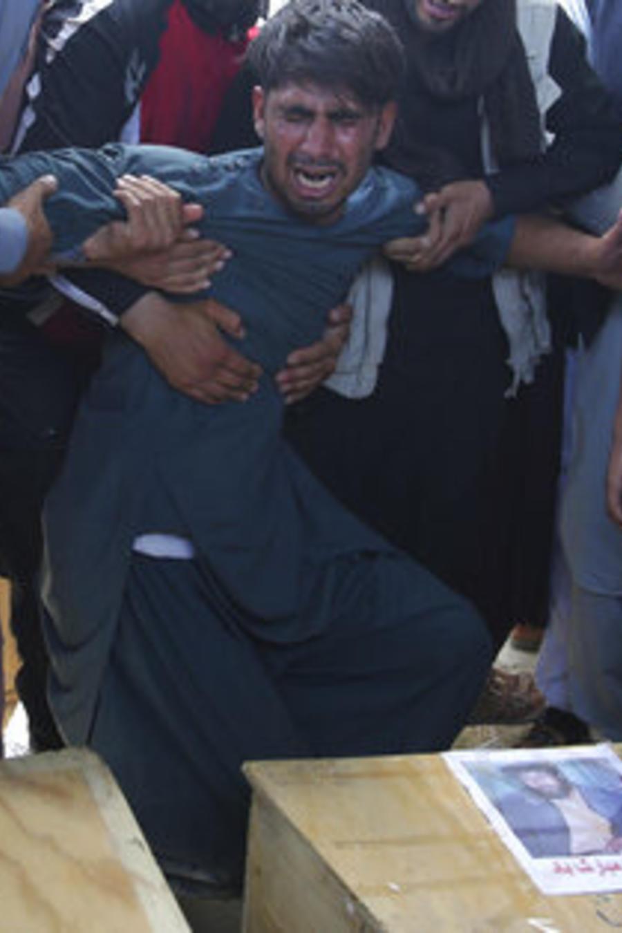 Un familiar llora las víctimas mortales de un ataque suicida que dejó este sábado a almenos 63 muertos en Kabul, Afganistán.