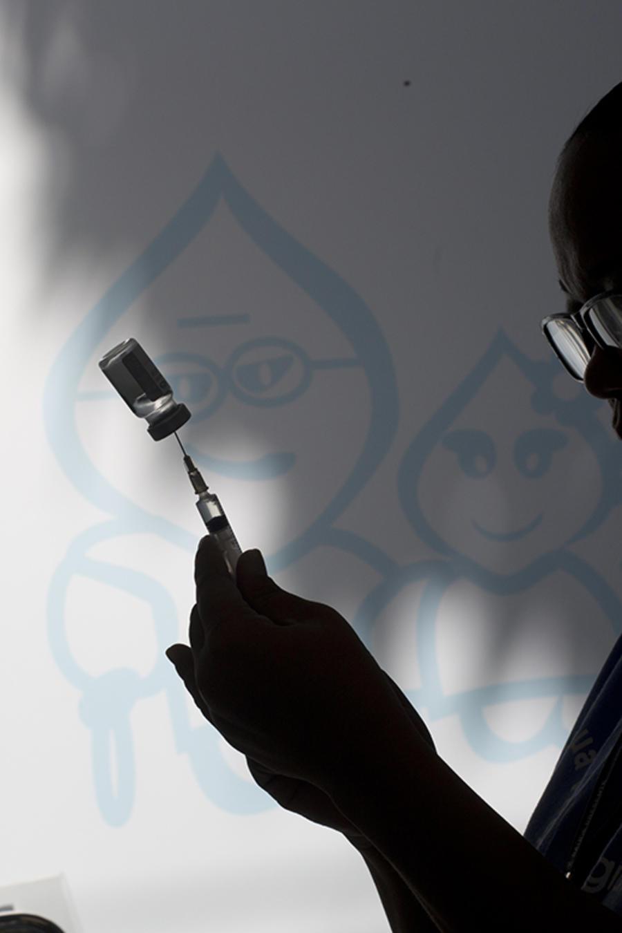 Una enfermera prepara una vacuna.
