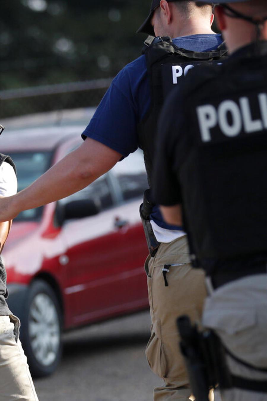La policía detiene a un individuo en la planta Koch Foods de Morton, Mississippi, el 7 de agosto del 2019.