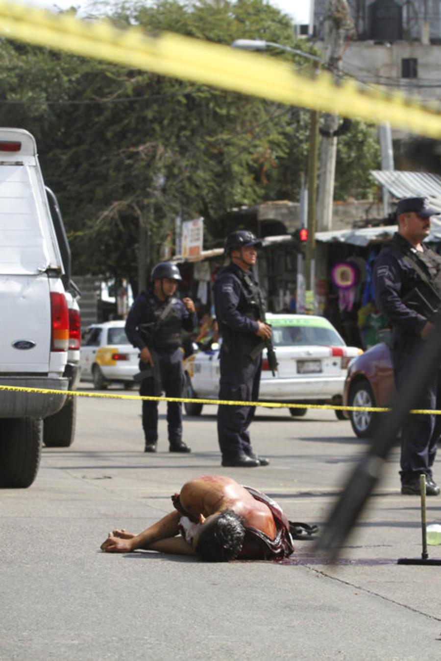 En esta imagen de archivo, tomada el 2 de junio de 2019, el cuerpo ensagrantado de un hombre yace tendido en el medio de una calle mientras la policía y los forenses protegen la escena, en Acapulco, México.