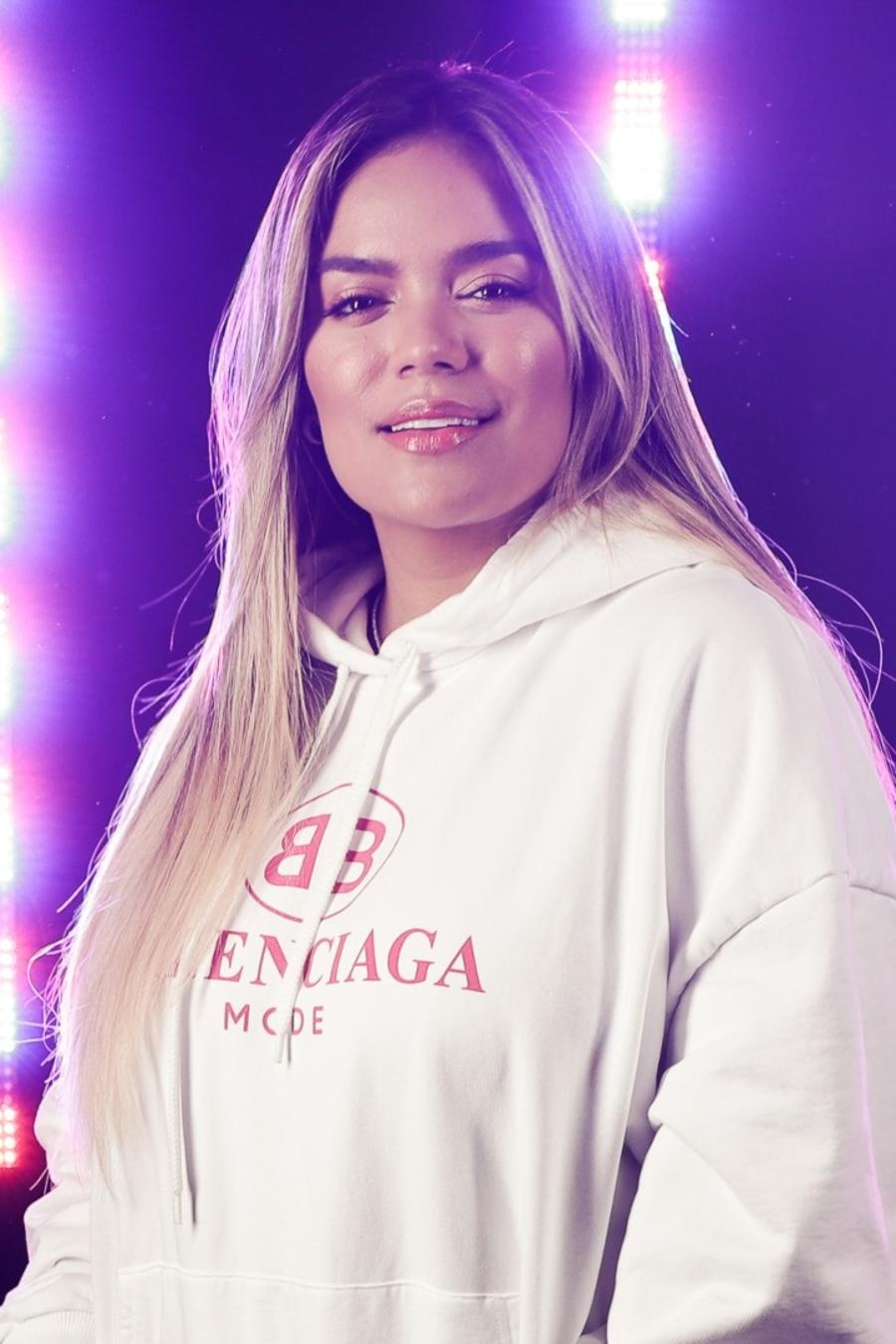 Karol G wearing a white hoodie and posing in front of lights