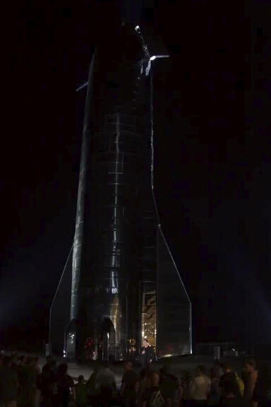 En esta imagen extraída de un video proporcionado por la compañía SpaceX, Elon Musk, en el centro, habla sobre la nave recién diseñada por laempresa en su centro de lanzamiento cerca de Brownsville, Texas, el sábado 28 de septiembre de 2019.